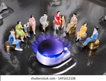 People doll sitting on coins around burning gas burners. Supply of natural gas to the population.