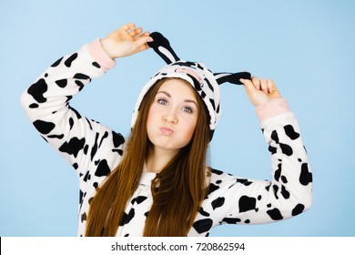 People dressed up like animals concept. Happy teenage girl in funny nightclothes cow pajamas costume, pyjamas cartoon style, smiling positive face expression, studio shot on blue.