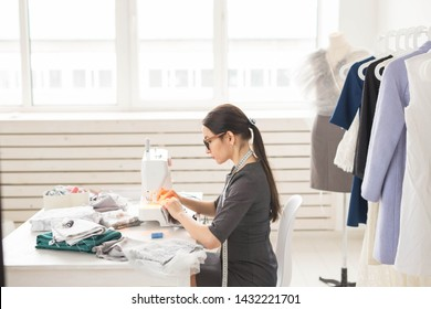 people, dressmaker, tailor, fashion and showroom concept - young fashion designer in her showroom