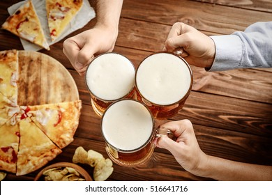 People drinking beer and eating pizza in pub