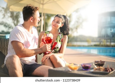People drinking a cocktail next to a swimming pool