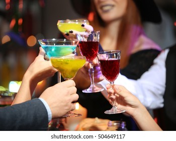 People drinking colorful cocktails at party, closeup. Halloween concept