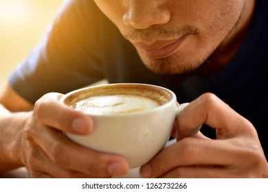 People are drinking Latte coffee on wooden table sunlight at window