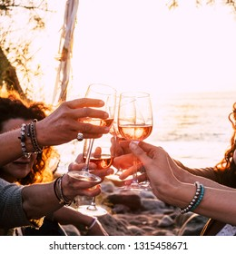 people drinking at party outdoor. group of friends white wine in hand toasting with glasses. close up on hands and drinks - beautiful scenic sunset and ocean in background for outdoor leisure