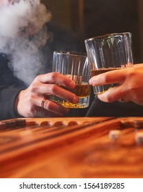 People drinking whiskey, smoking hookah and playing backgammon in bar. Couple resting together after hard day.