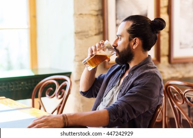 people, drinks, alcohol and leisure concept - happy young man drinking beer from glass at bar or pub