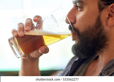 people, drinks, alcohol and leisure concept - close up of young man drinking beer from glass at bar or pub