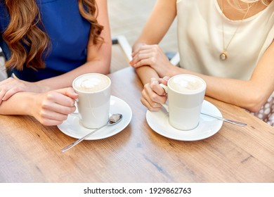 people, drinks and friendship concept - close up of young women with coffee cups at street cafe