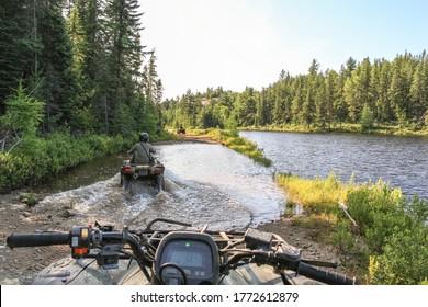 People driving ATV quadbike through water. Lake in Ontario, Canada.