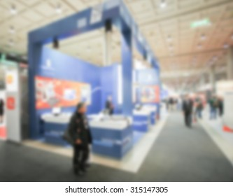 People during an event, intentionally blurred background.