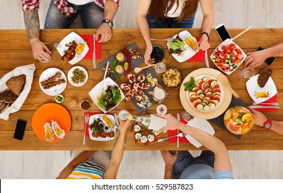 People eat healthy meals at served festive table served for party. Friends celebrate with organic food on wooden table top view. Drink wine and have fun together