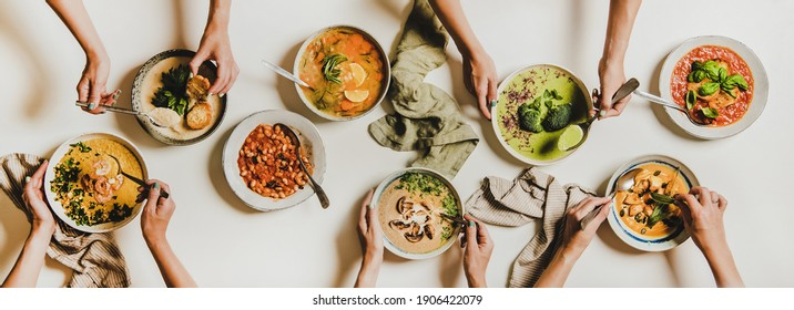 People eating Autumn and Winter creamy vegan soups. Flat-lay of peoples hands with homemade soup and bread slices over white table background, top view. Fall and Winter food menu, vegetarian food