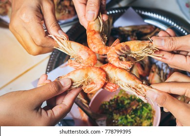 people are  eating  grilled shrimp with fun and happy in holiday.