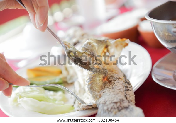 people eating grilled snakehead fish - Thailand