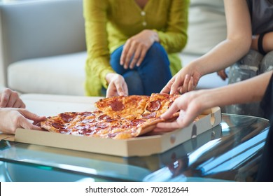 People eating pizza at home, unrecognizable persons