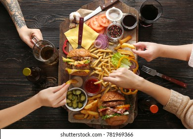 People eating tasty double burgers and other snacks, top view