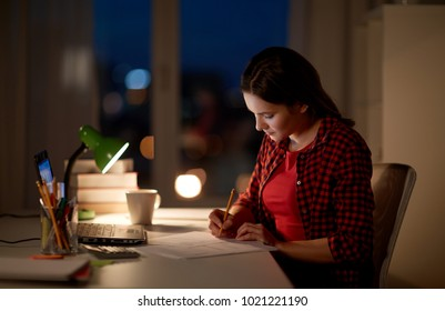 people, education, freelance and learning concept - woman or student girl with laptop computer writing to notebook at home at night
