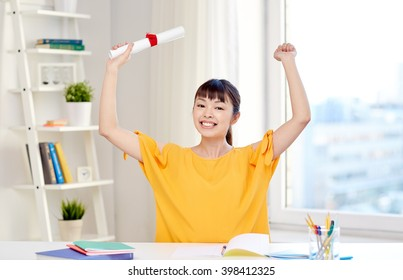 people, education, school, graduation and learning concept - happy asian young woman student with diploma scroll celebrating at home