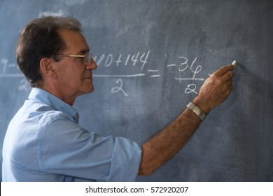People and education. Teacher writing on math equation on blackboard during lesson.