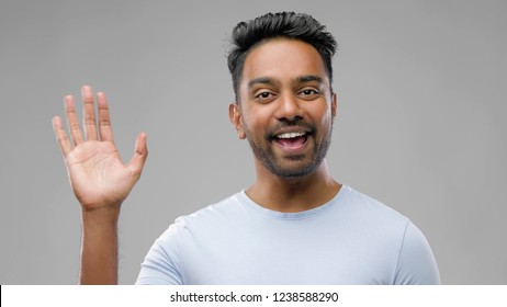 people, emotion and facial expression concept - happy smiling indian man waving hand over grey background