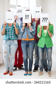 people, emotions and communication concept - group of friends or students covering faces with paper sheets