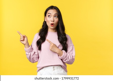 People emotions, lifestyle and fashion concept. Amazed and excited stylish asian female say wow, looking and pointing upper left corner interested in promo banner product, yellow background