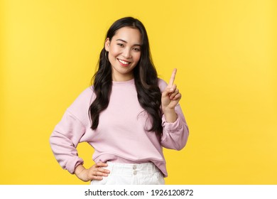 People emotions, lifestyle and fashion concept. Smiling happy good-looking asian girl giving advice, showing one finger as explain rules, make point, standing yellow background