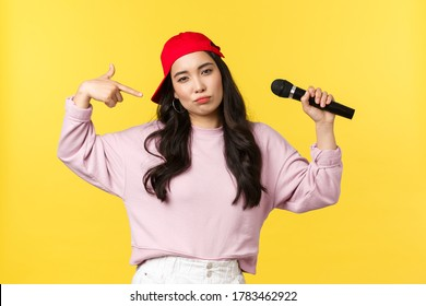 People emotions, lifestyle leisure and beauty concept. Cool and sassy stylish female raper, girl singer in red cap, acting confident, holding microphone and pointing at herself to show-off