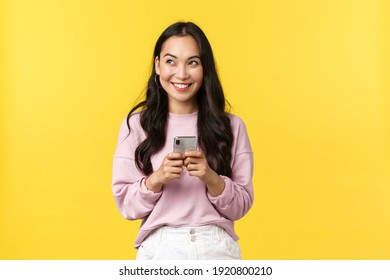 People emotions, lifestyle leisure and beauty concept. Dreamy and excited happy young asian woman using mobile phone, smiling and looking upper left corner thoughtful, have idea