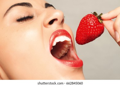 people, emotions, natural, food, beauty and lifestyle concept - Sexy Woman Eating Strawberry. Sensual Lips. Manicure and Lipstick. Desire. Beauty Girl Sexy Lips with Strawberry. white teeth