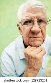 people and emotions, portrait of depressed senior hispanic man with glasses looking at camera, leaning with hands on chin