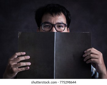 People and emotions, portrait of nerd man with glasses looking at camera he has a black book for conceal one's face,Copy space.