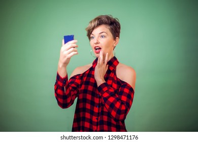 People and emotions - a portrait of smiling young woman with short hair looking at mirrow and correcting makeup