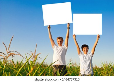people with empty billboards in a meadow