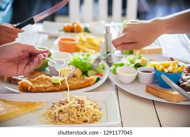 People enjoy eat spaghetti and steak together in a big meal set - family happy time with food concept