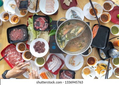 People enjoy eating Shabu Sukiyaki, Japanese food together top view.