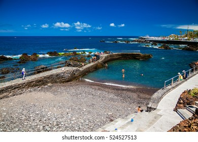 people enjoy the good weather on the beach of San Telmo in Puerto de la Cruz, Tenerife, Spain