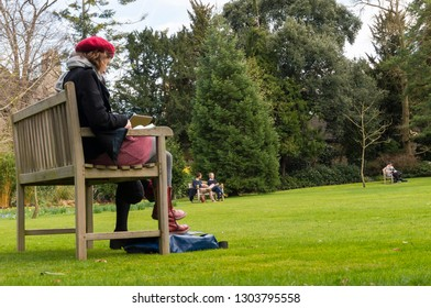 People enjoy sunny weather in a park in Oxford City, England. It is a sunny spring day.