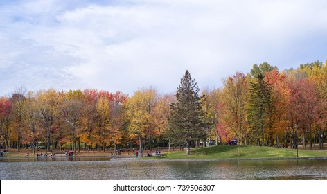 People enjoy a warm autumn day at the Beaver Lake in Mont Royal Park, Montreal