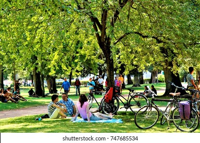 people enjoyed summer afternoon hours under trees in the park aside Annecy Lake, Annecy, France, July 30, 2015