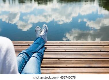 People enjoying beautiful nature. Woman relaxing her feet on a wooden dock.