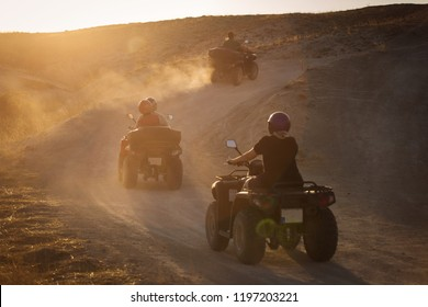 People enjoying driving atv on sunset in Valleys of Cappadocia with lot of dusts in background.