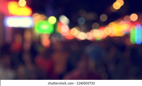 People enjoying famous Bourbon Street at night in the French Quarter of New Orleans, Louisiana, blurred