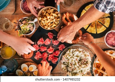 People enjoying friends concept - Tasty lunch or dinner concept with top view table full of delicious food and friends people taking and serving to eat together - coloured and wooden background