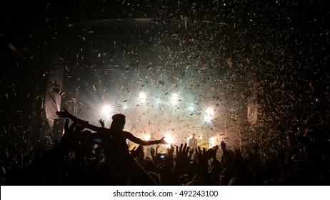 People enjoying good music at a concert - confetti falling