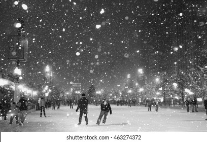 People enjoying ice skating at Millennium park ice rink during snowy night in Chicago. Horizontal black-and-white shot.