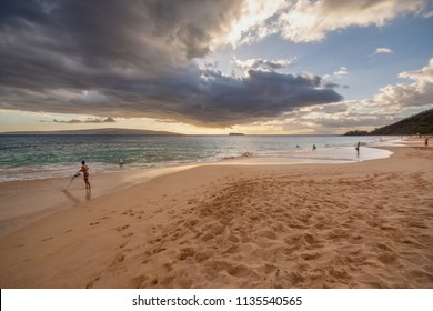 People enjoying Makena Beach during a dramatic sunset in Maui, Hawaii, US.
