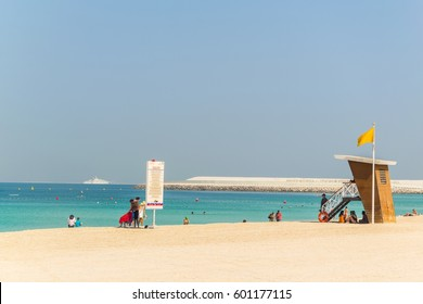People are enjoying a sunny day on a beach in Dubai, UAE