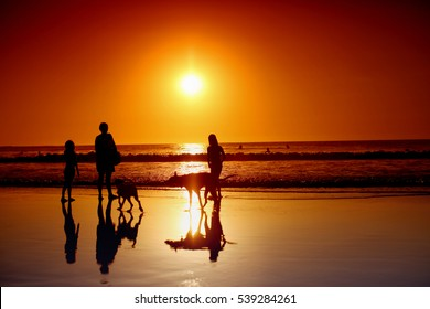 People enjoying a sunset at the beach. Focused on the water.