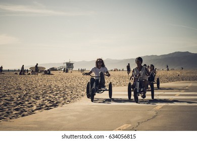 People enjoying the warm weather with their beach cruiser trikes at the Venice Beach promenade in Los Angeles California, US / June 2016